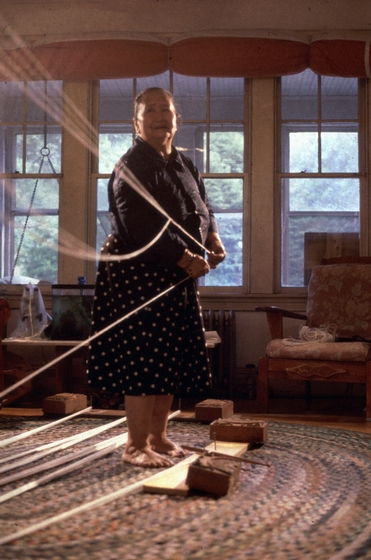 Yang Fang Nhu measures threads in her home, Providence, Rhode Island, August 1985, photograph by Winifred Lambrecht, courtesy Rhode Island State Council on the Arts