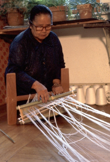 Yang Fang Nhu prepares her loom in her home, Providence, Rhode Island, August 1985, photograph by Winifred Lambrecht, courtesy Rhode Island State Council on the Arts