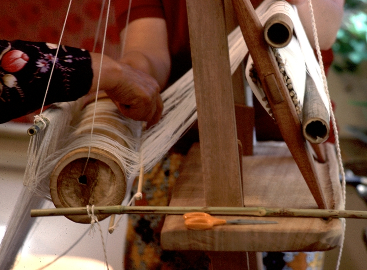 Yang Fang Nhu prepares her loom for weaving in her home.  Providence, Rhode Island, August 1985, photograph by Winifred Lambrecht, courtesy Rhode Island State Council on the Arts
