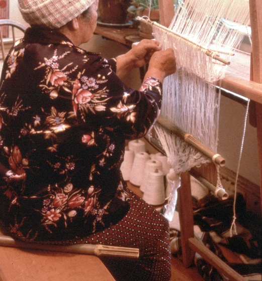 Yang Fang Nhu straightens the needles on her loom, Providence, Rhode Island, August 1985, photograph by Winifred Lambrecht, courtesy Rhode Island State Council on the Arts