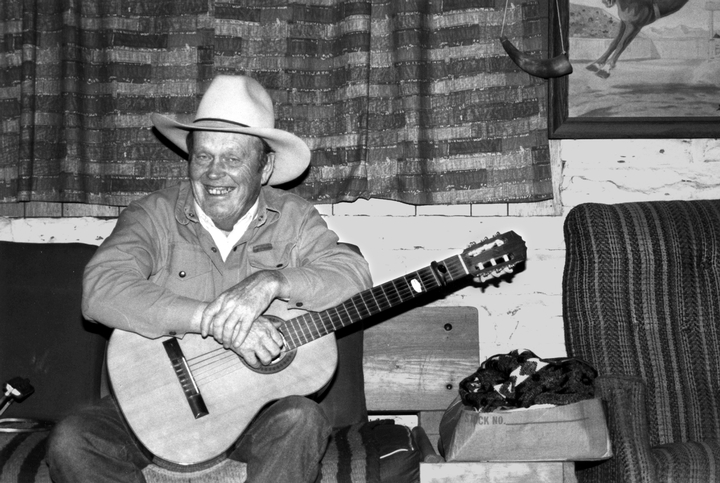 Cowboy singer and storyteller Glenn Ohrlin's repertoire ranged from old ballads to popular country and Western songs. He was also an illustrator and once made extra money by painting signs for businesses that wanted to attract cowboys as customers. He is pictured here in his living room, Mountain View, Arkansas, 1991, photograph by Alan Govenar