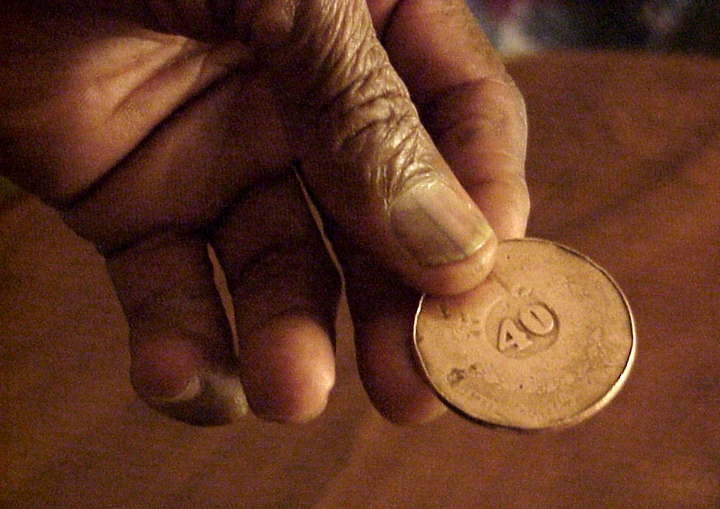 João Oliveira dos Santos (Mestre João Grande) holding the coin he uses as a pick when playing the *berimbau*, Arlington, Virginia, 2001, photograph by Alan Govenar