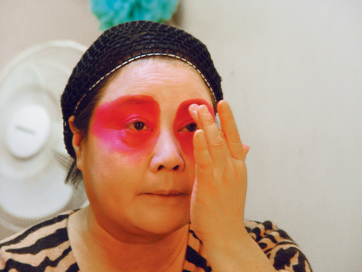 Qi Shu Fang applying a red color around her eyes in her dressing room at the Kaye Playhouse in midtown Manhattan, New York, 2002, photograph by Alan Govenar