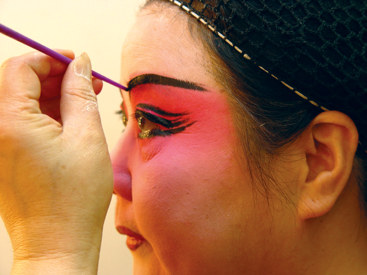 Qi Shu Fang applying black eyebrow liner in her dressing room at the Kaye Playhouse in midtown Manhattan, New York, 2002, photograph by Alan Govenar