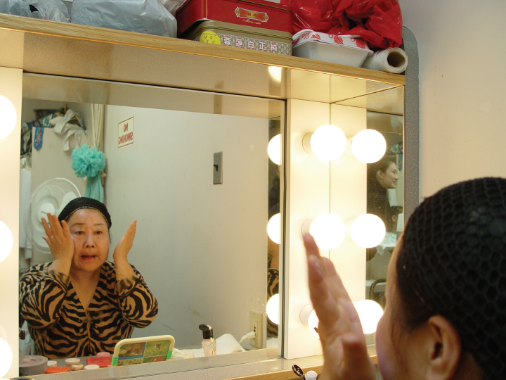Qi Shu Fang applying the foundation for her makeup in her dressing room at the Kaye Playhouse in midtown Manhattan, New York, 2002, photograph by Alan Govenar