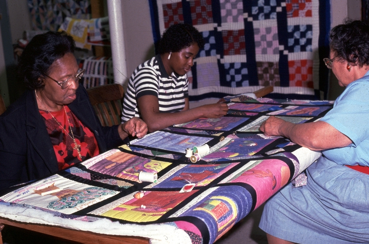Hystercine Rankin helps to quilt a top made of children's illustrations of African American stories. Joining Rankin are Loraine Marks and Helen Cates, a retired teacher. Rankin taught regularly at Mississippi Cultural Crossroads, Port Gibson, Mississippi. 1991, photograph by Patricia Crosby, courtesy Mississippi Cultural Crossroads and National Endowment for the Arts
