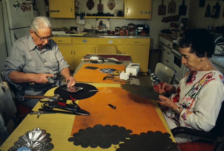 Emilio Romero learned tinsmithing in the Civilian Conservation Corps during the Great Depression and worked with tin full time after he retired. His wife, Senaida, embroidered *colchas* (coverlets) and sometimes placed them in ornamented tin frames that he created. Santa Fe, New Mexico, 1984, photograph by Eduardo Fuss, courtesy Marie Cash