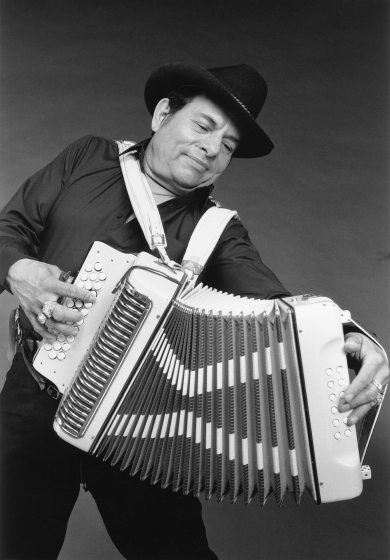 "Domingo 'Mingo' Saldivar is known as ""The Dancing Cowboy"" because he wears his accordion slung low on his body and moves as he plays. He discovered that country music has much in common with the conjunto  of his native South Texas and rouses audiences with such tunes as Johnny Cash's ""Ring of Fire."" Photograph by Michael Young, 1992, courtesy National Endowment for the Arts"