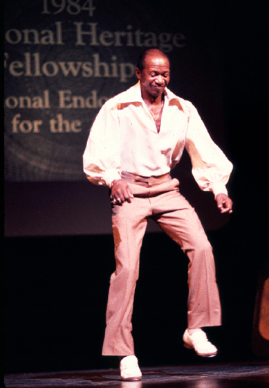 "Howard 'Sandman' Sims started as a street dancer and, throughout his career, liked to return to his roots and  participate in ""challenge dances"" on Harlem street corners. His specialty was dancing on a board lightly sprinkled with sand, producing a cool, slippery sound. 1984 National Heritage Fellowship Ceremonies, courtesy National Endowment for the Arts"
