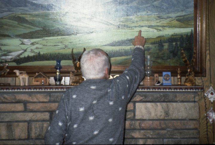 On a painting of the Carpathian Mountains that hung in Eudokia's living room, Dmytro Sorochaniuk points out the location of the villages where he and his wife grew up. His son-in-law painted the picture. Courtesy New Jersey State Council on the Arts