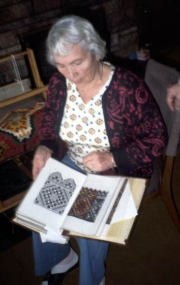 Eudokia Sorochaniuk holds the album with embroidery stitches she had made. In it she had recorded Hutsul *nyz* designs by stitching them in a dark corner so that a learner could count the threads to make the design. She then stitched in the colors on half of the design so that the student would know the traditional colors. Courtesy New Jersey State Council on the Arts