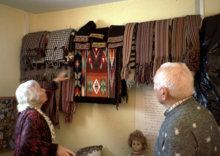 Eudokia and Dmytro Sorochaniuk stand beneath a row of Eudokia's woven pieces, courtesy New Jersey State Council on the Arts