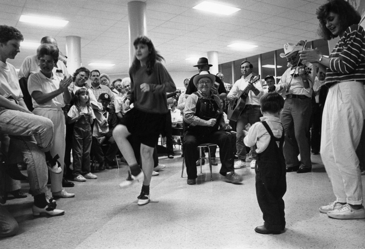 Robert Spicer playing spoons for a young dancer at the Tennessee State Fiddle Contest, Clarksville, Tennessee, April 8, 1989, photograph by Robert Cogswell, courtesy Tennessee Arts Commission