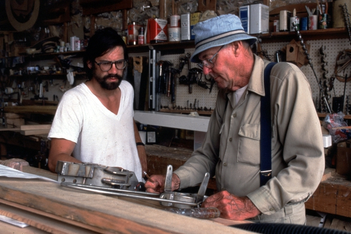 In his boat shop, Ralph W. Stanley discusses the arrangement of mast fittings for a Friendship sloop with metalsmith Dave Brown. Southwest Harbor, Maine, 1998, photograph by Peggy McKenna, courtesy National Endowment for the Arts
