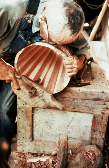Alex Stewart at work in his shop, using a rasp to smooth the outer edges of the top and bottom of a butter churn, Sneedville, Tennessee, ca. 1975-79, photograph by Roy Overcast, courtesy Tennessee Arts Commission