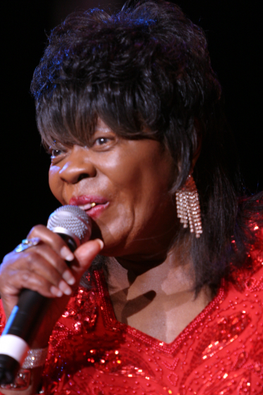"Singer Koko Taylor was ""born and raised with the blues"" on a cotton farm in the Mississippi Delta and joined the migration to Chicago, where she remained popular even as blues faded among African Americans. Despite health problems and her husband's death, she continued to perform and record, taking particular delight in being a role model for young people. 2004 National Heritage Fellowship Concert, Washington, D.C., photograph by Michael G. Stewart, courtesy National Endowment for the Arts"