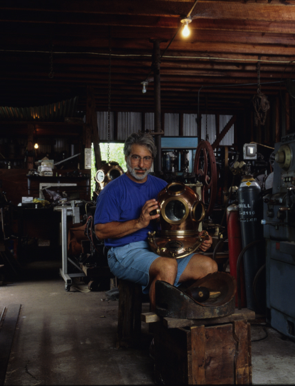 Nicholas Toth is one of the few craftsmen still making the traditional one-piece spun-copper diving helmet known as the hard hat. He practices what his grandfather taught him, making helmets that rise above the functional to become works of art. He's shown here in his Tarpon Springs, Florida, workshop with a completed helmet. Courtesy Florida Folklife Program