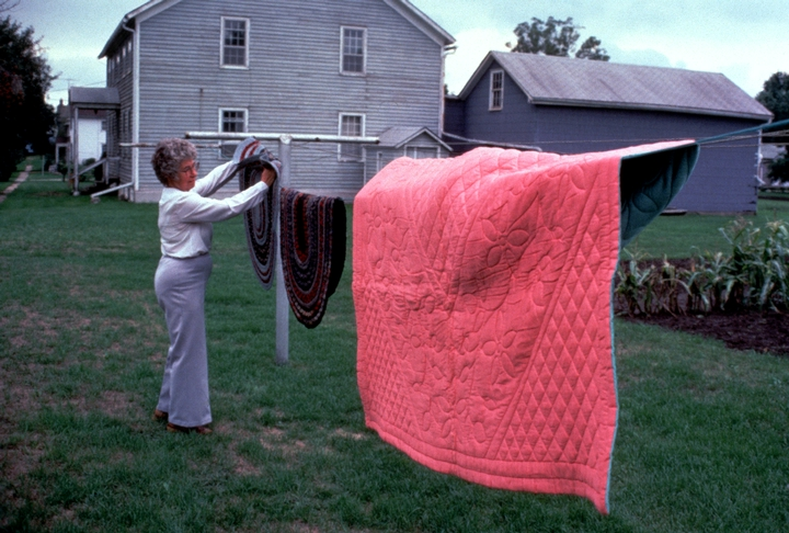 Dorothy Trumpold hanging rugs and a quilt in her yard, East Amana, Iowa. Photograph by Steven Ohrn, courtesy National Endowment for the Arts