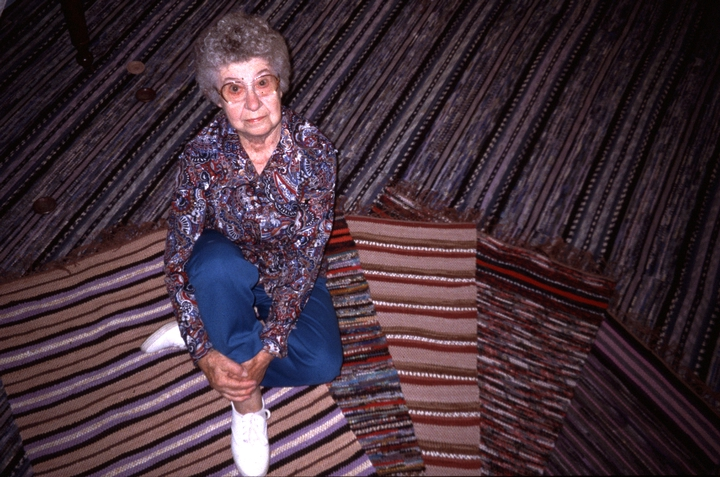 Dorothy Trumpold sitting on some of her rugs in her home, East Amana, Iowa, photograph by Steven Ohrn, Courtesy National Endowment for the Arts