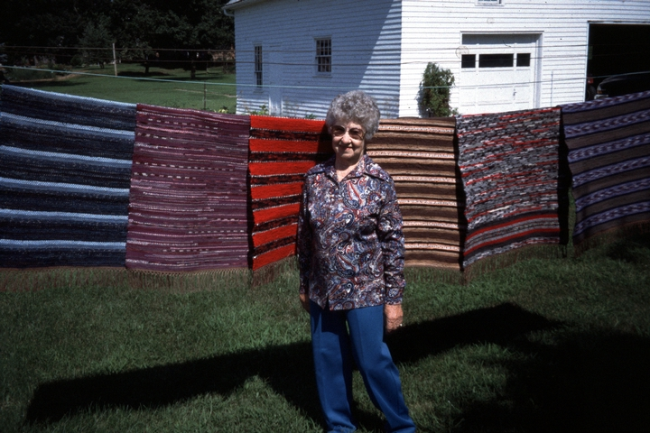 Dorothy Trumpold standing in front of some of her rugs hanging in her yard, East Amana, Iowa, photograph by Steven Ohrn, Courtesy National Endowment for the Arts