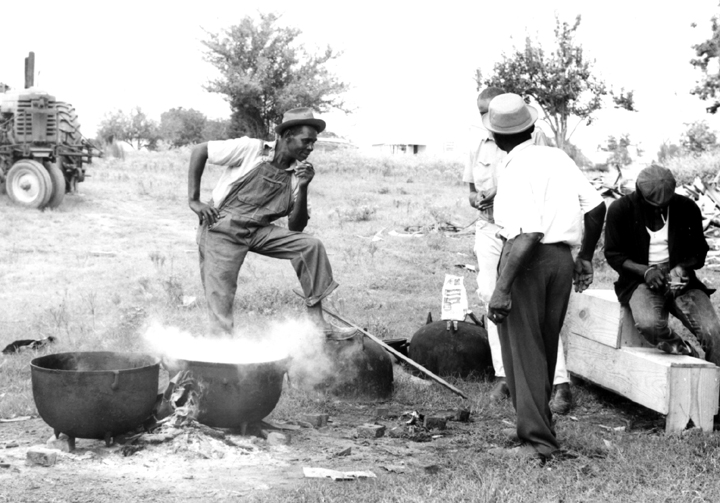 Othar Turner talking with his friends while cooking barbecue for a picnic, Senatobia, Mississippi, 1970, photograph by David Evans
