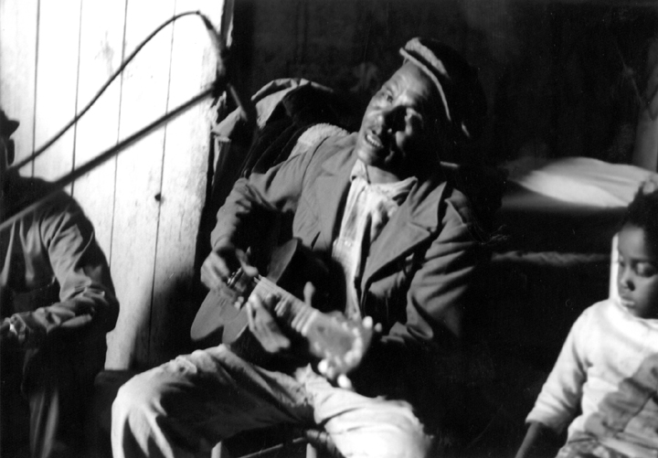 Othar Turner playing the guitar, Senatobia, Mississippi, 1969, photograph by David Evans