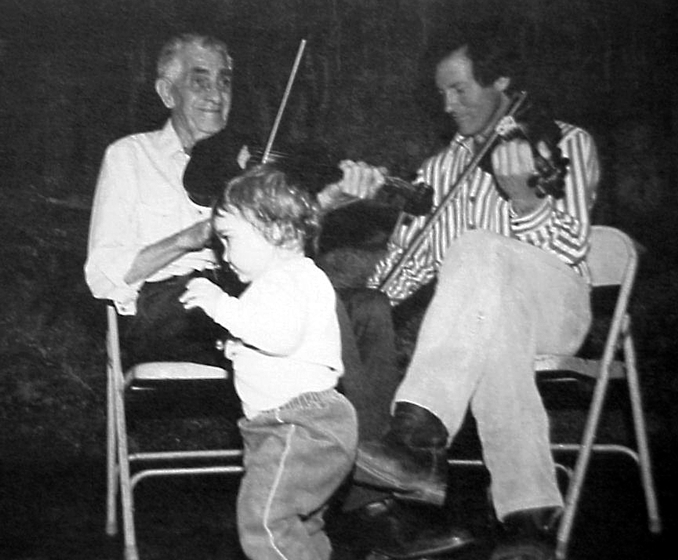 'Passing good music and sound values down to younger generations are important in Melvin Wine's mature years. Here he plays with apprentice John Gallagher for the obvious enjoyment of great-granddaughter Danielle.' Photograph and comments by Susan Leffler, courtesy *Goldenseal* magazine