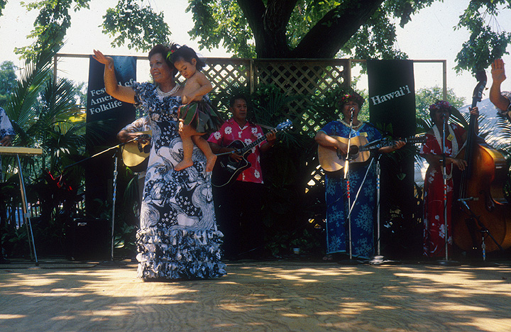 The Zuttermeister Family — Hawaiian Hula Dance. Chanter: Emily Kaui'i Zuttermeister, *kumu hula*, teacher. Dancers: Noenoelani Zuttermeister Lewis, Emily's daughter, and Hauolionani Zuttermeister, Emily's granddaughter. 1989 Festival of American Folklife, photograph by Dane Penland, courtesy Ralph Rinzler Folklife Archives and Collections, Center for Folklife and Cultural Heritage, Smithsonian Institution