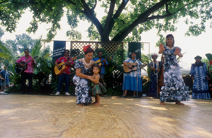 The Zuttermeister Family — Hawaiian Hula Dance. Chanter: Emily Kaui'i Zuttermeister, *kumu hula*. Dancers: Noenoelani Zuttermeister Lewis, Emily's daughter, and Hauolionani Zuttermeister, Emily's granddaughter. 1989.  Photograph by Laurie Minor, courtesy Ralph Rinzler Folklife Archives and Collections, Center for Folklife and Cultural Heritage, Smithsonian Institution