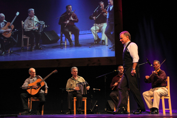 Kevin Doyle tap dancing while Séamus Connolly performs in the background at the 2013 National Heritage Fellowship Concert, Washington, D.C., photograph by Michael G. Stewart