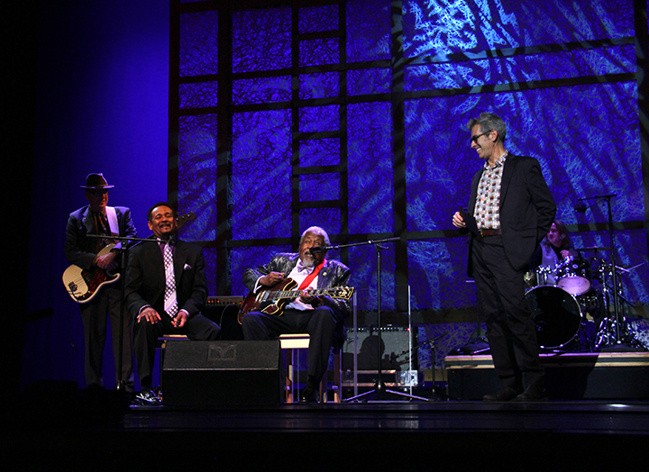 Marco Werman introducing Drink Small and his band at the 2015 National Heritage Fellowship Concert, Washington, D.C., photograph by Michael G. Stewart.