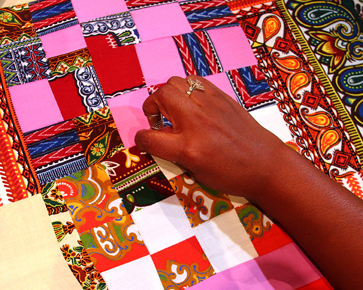 Claudine Pettway showing one of her quilts at the 2015 National Heritage Fellowship Concert, Washington, D.C., Photograph by Michael G. Stewart.