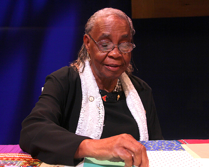 Mary Lee Bendolph singing and quilting at the 2015 National Heritage Fellowship Concert, Washington, D.C., Photograph by Michael G. Stewart.