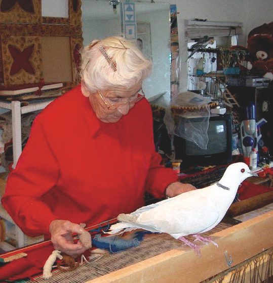 Eppie weaves one of her colorful tapestries as her dove looks on, courtesy of Ruben Archuleta  