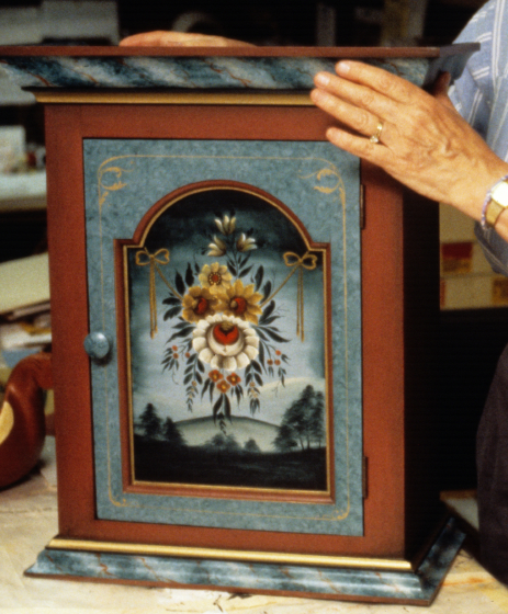 Eldrid Arntzen showing the front of the wooden chest, which is painted in Valdres style, photograph by Gale Zucker