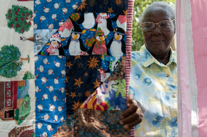 Laverne Brackens checking her quilts hanging on a clothes line in her backyard, Fairfield, Texas, July 6, 2011, photograph by Alan Govenar