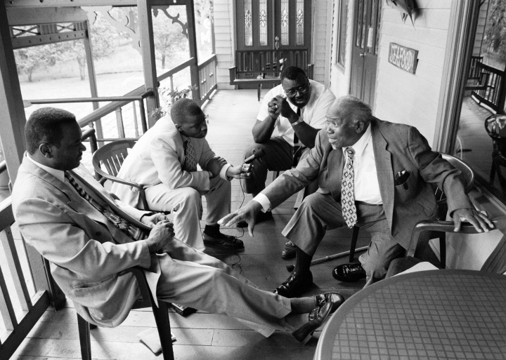 Willie Eason regales (left to right) Chuck, Carlton and Phil Campbell with tales of bygone days when he traveled widely to play for worship services, revivals and street corner music ministries, Crescent City, Florida 1998. photograph by Robert L. Stone