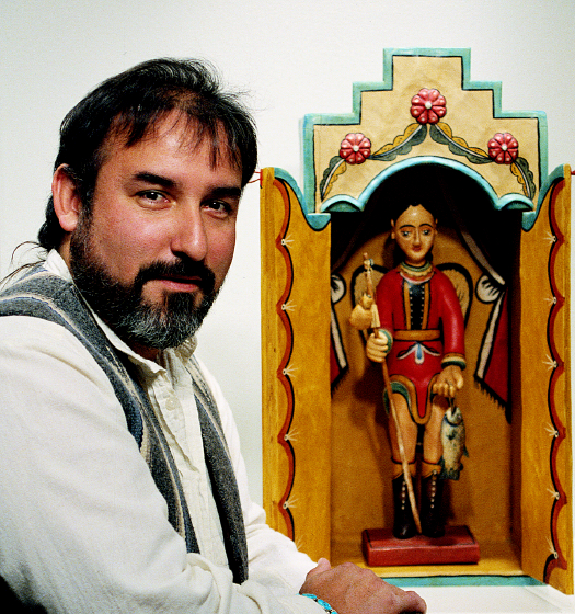 "Charles Carrillo posing with his San Rafael en Nicho/Sain Rafael bulto, 1992 (23.5"" tall), photograph by Robert Reck, courtesy LPD Press and <www.nmsantos.com>"