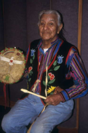 Francis Cree in a studio recording songs and traditional stories for the NDCA-produced enhanced CD 'The Elders Speak.' The drum is painted with a rose for his wife, an eagle for his heart (Francis' Chippewa name is Eagle Heart), and a turtle above a geometric design representing the Turtle Mountains of north central North Dakota from which he came. The Turtle Mountains are said to have originated upon the back of a great turtle after a huge flood, and traditionalists refer to the area as 'Turtle Island' in reference to the flood story. Turtle Mountain Indian Reservation, North Dakota, courtesy North Dakota Council on the Arts
