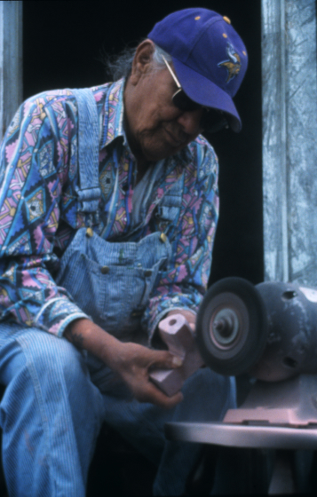 Francis Cree makes a man's pipe out of red Catlinite stone. Men's pipes are L-shaped, while women's pipes are T-shaped. The stone (bowl) is carved in an eagle shape, and the bowl part for the tobacco is carved in the shape of a heart, again, referencing Francis' Chippewa name, Eagle Heart. Turtle Mountain Indian Reservation, North Dakota, courtesaay North Dakota Council on the Arts