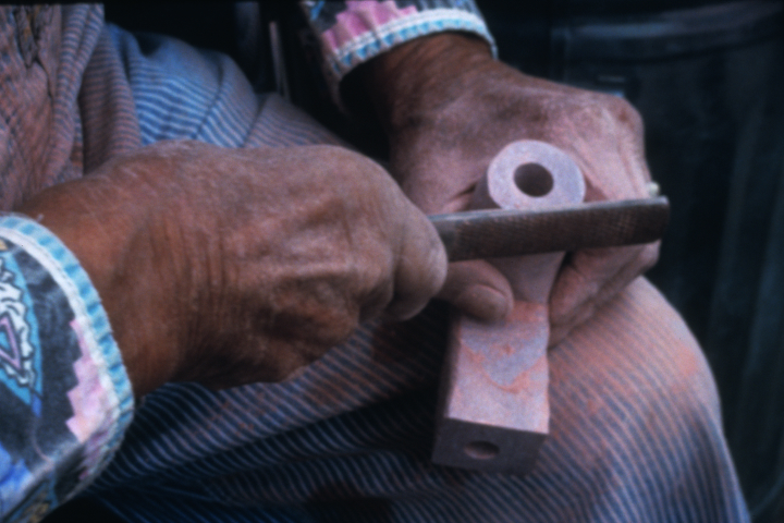 Francis Cree makes a man's pipe out of red Catlinite stone. Men's pipes are L-shaped, while women's pipes are T-shaped. The stone (bowl) is carved in an eagle shape, and the bowl part for the tobacco is carved in the shape of a heart, again, referencing Francis' Chippewa name, Eagle Heart. Turtle Mountain Indian Reservation, North Dakota, courtesy North Dakota Council on the Arts