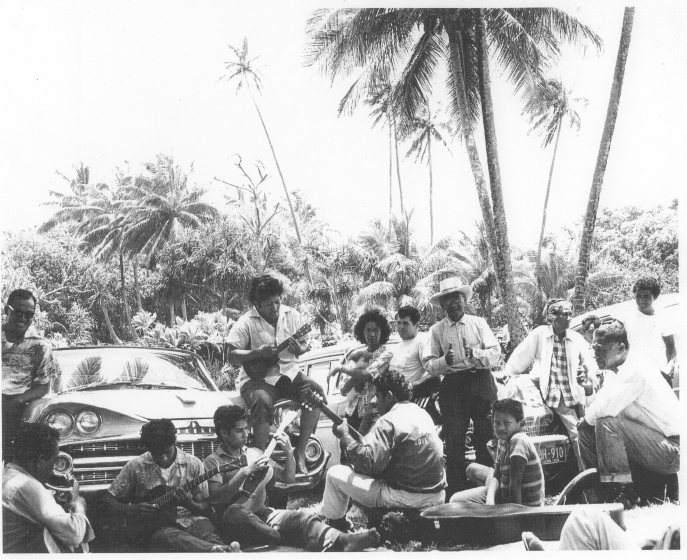 Ledward Kaapana family gathering at Harry K. Brown State Park, 1958. Ledward is the left-most of the two boys sitting on the ground in front of the car. His mother, Mama Tina Kaapana, is sitting on the fender. Legendary Uncle Fred Punahoa is clapping and wearing a lauhala hat, courtesy Ledward Kaapana