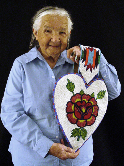 Agnes 'Oshanee' Kenmille spent most of her life on the Flathead Reservation in Montana, where she practiced and taught beadwork and tanning, but she received orders from all over the world. Among those who have worn her gloves are Muhammad Ali and Al Gore. Shown here with one of her hand-crafted handbags, Arlington, Virginia, 2003, photograph by Alan Govenar
