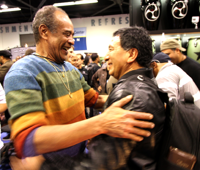 Carlinhos Pandeiro de Ouro encounters his friend, renowned percussionist Alex Acuña, at NAMM 2010, photograph by Roger Poirier