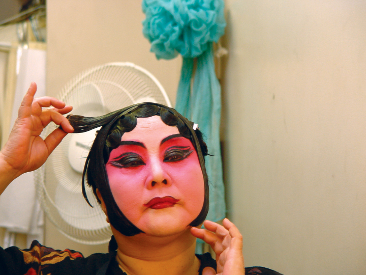 Qi Shu Fang pastes plaits of hair to create a traditional face line in her dressing room at the Kaye Playhouse in midtown Manhattan, New York, 2002, photograph by Alan Govenar
