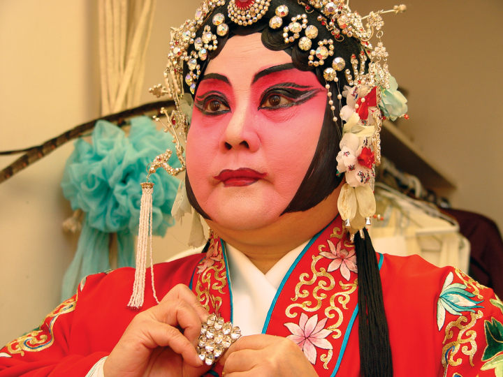 Qi Shu Fang places a last piece of jewelry on her costume in her dressing room at the Kaye Playhouse in midtown Manhattan, New York, 2002, photograph by Alan Govenar