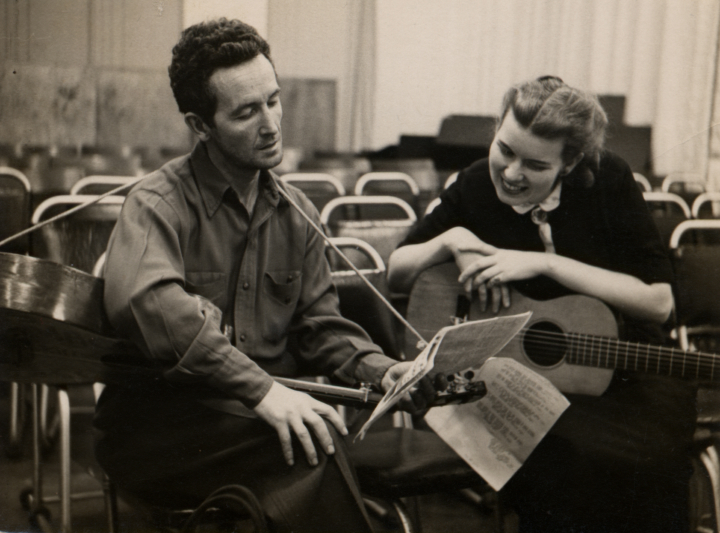 Woody Guthrie shows Jean Ritchie his latest song, 'Written on My Way Down Here,' at an Oscar Brand Folksong Festival broadcast, WNYC, New York City, ca.1948. Courtesy Jean Ritchie and George Pickow