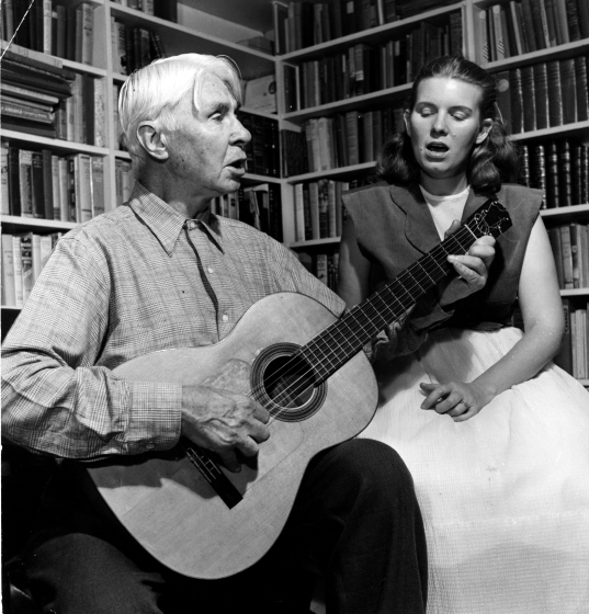 Jean Ritchie and Carl Sandburg. About this photograph, Jean recalled, 'On impulse while driving through North Carolina we called Carl Sandburg at his Flat Rock farm; we had recently met him at Frank Warner's apartment in New York. He said, 'Come right over; we'll have some goat's milk for supper!' The visiting and singing went on and it ended with our spending the night, sleeping in 'The Crow's Nest' at the top of the house where Carl did most of his writing during that period.' Courtesy Jean Ritchie and George Pickow