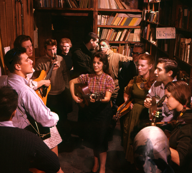Opening night of Izzy Young's Folklore Center on MacDougal Street in Greenwich Village, (left to right) Jerry Silverman, Cynthia Gooding, unknown, Una Ritchie Yahkub (Jean's sister), two unknown men, Carolyn Hester in front, Jean Ritchie, Happy Traum, Molly Scott, courtesy Jean Ritchie and George Pickow