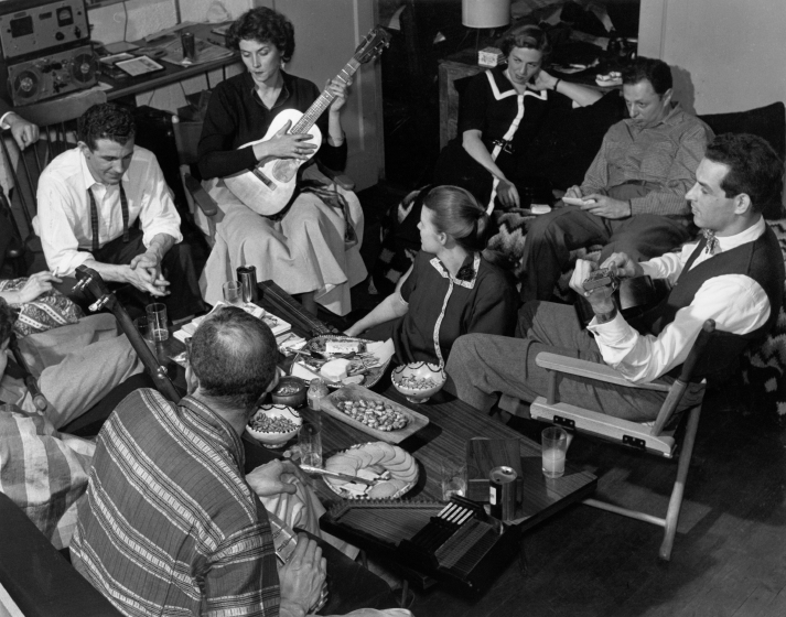 About this photograph, Jean Ritchie said, 'George takes a picture of an informal singing party in our first apartment, 88 Seventh Avenue South, in the Village.' Recognizable faces (left to right): Tom Clancy, Robin Roberts, Jean (on floor), Mrs. Amen and husband-artist Irving Amen, Oscar Brand. Photograph by George Pickow, courtesy Jean Ritchie and George Pickow